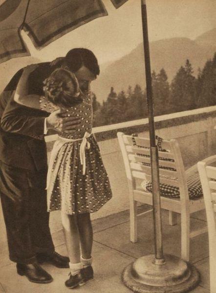A small German girl hugs Adolf Hitler.