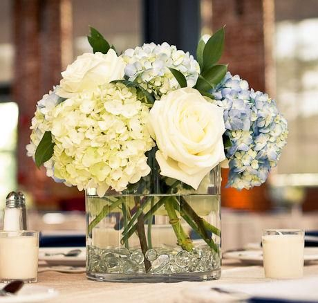 loosely-arranged flowers: hydrangeas and roses in clear square short vases with clear stones in the bottom
