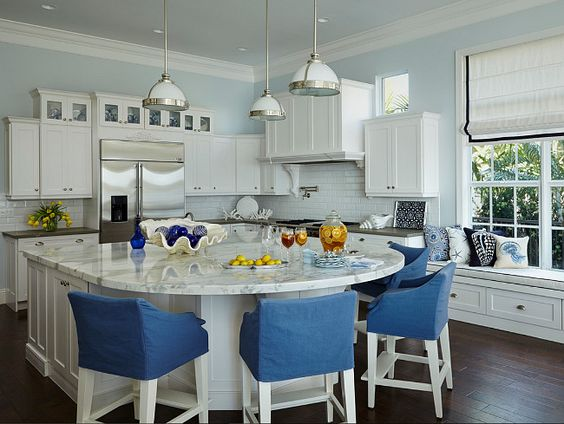 Blue and white Kitchen. In this blue and kitchen, Lee Industries stools surround the Carrara marble island top, refinished by Mario Ferazzoli & Son. Samuel & Sons tape outlines the Roman shades in Duralee fabric. Wellborn Cabinet's cabinetry from DeStefano Designs and Restoration Hardware pendants already existed in the home.