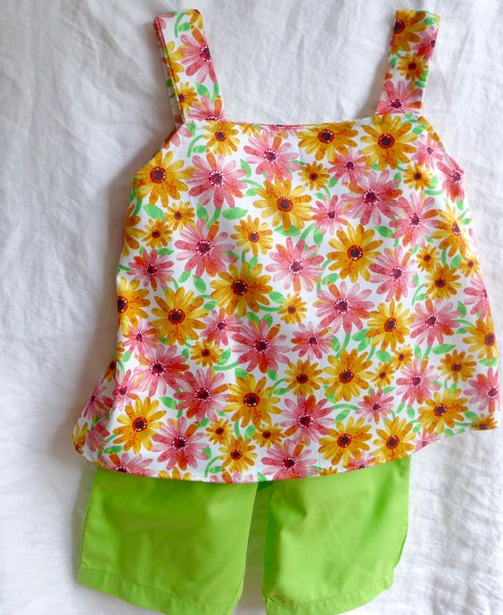 This two piece summer outfit in multi coloured floral cotton top and knee length shorts is perfect for summertime.  The top is pink, orange, yellow and green daisies with shoulder straps that button at the back.  CA$17.00