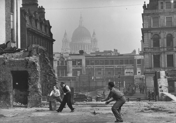 A group of men playing cricket on a blitzed site in Blackfriars, London, during their lunch-hour, with St Paul's Cathedral in the background. 1940s