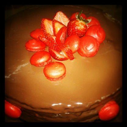Mouse de chocolate decorado con fresas naturales y macarrones rojos