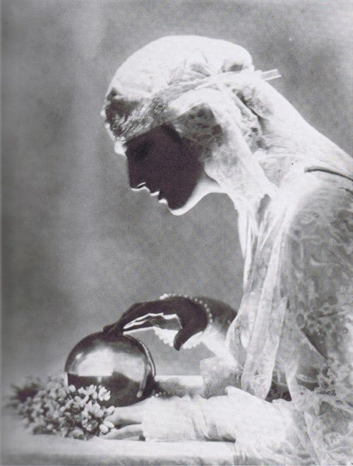 vintage fortune teller psychic reading her crystal ball white lace dress headwrap