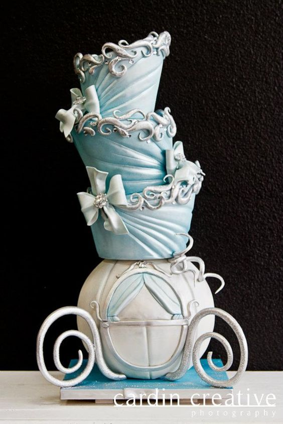 """""""Cindy"""" ... a whimsical take on a fairytale classic. Topsy turvy design with blue ruche, silver curls, and bows.. all atop the signature pumpkin carriage."""