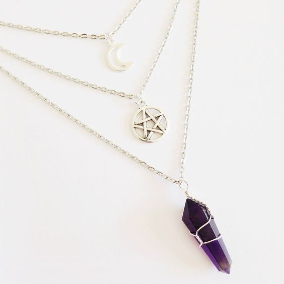A triple layer necklace with a moon pendant, a pentagram pendant and a wire wrapped Amethyst crystal point.