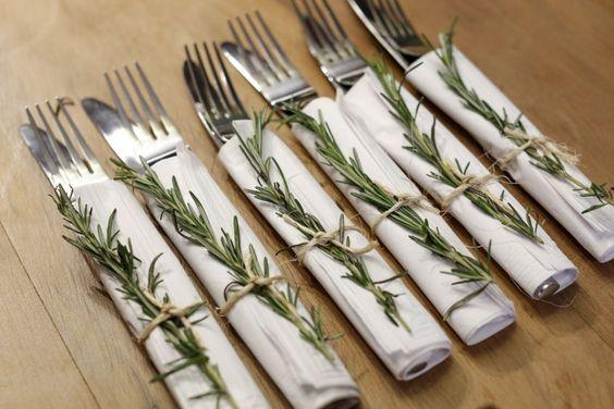 Envolvemos os talheres de cada convidado nos charmosos guardanapos de papel da Relevo Guardanapos e amarramos com um raminho de alecrim e ráfia. Colocamos parte dos pares de garfo e faca em uma cesta quadrada toda de rattan.