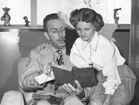 """hotograph caption reads: """"Kathryn Beaumont shown with Walt Disney"""". Mr. Disney has two copies of Alice in wonderland, one of which he is showing to 11-year-old Kathryn who is signed as the voice of Alice in Walt Disney's cartoon feature production of the book. Photograph dated June 9, 1949."""