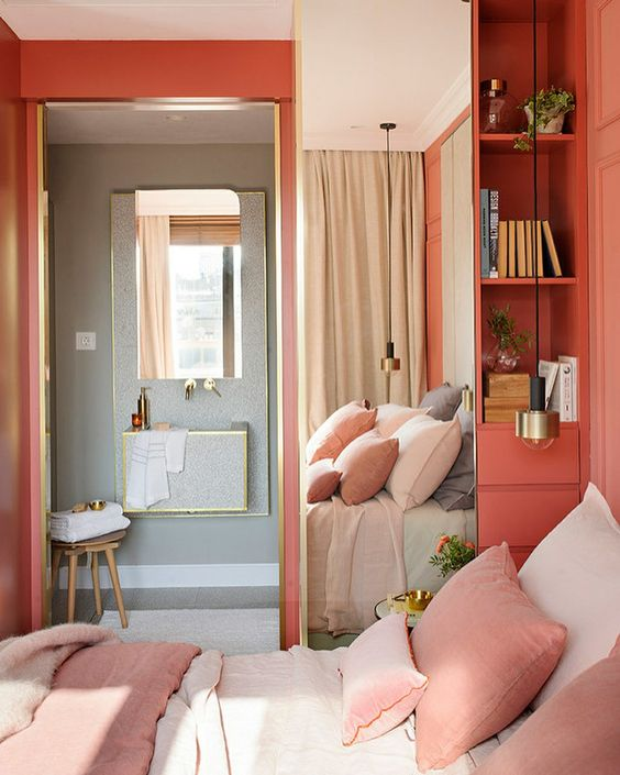 Loving the coral colored walls in this bedroom