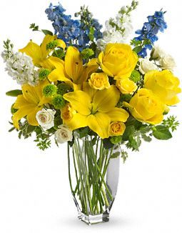 Meet Me in Provence by Teleflora. Flowers  Sunny yellow asiatic lilies and roses are blended with light blue delphinium, white stock, white roses and green button spray chrysanthemums in a clear glass Jewel Vase.: