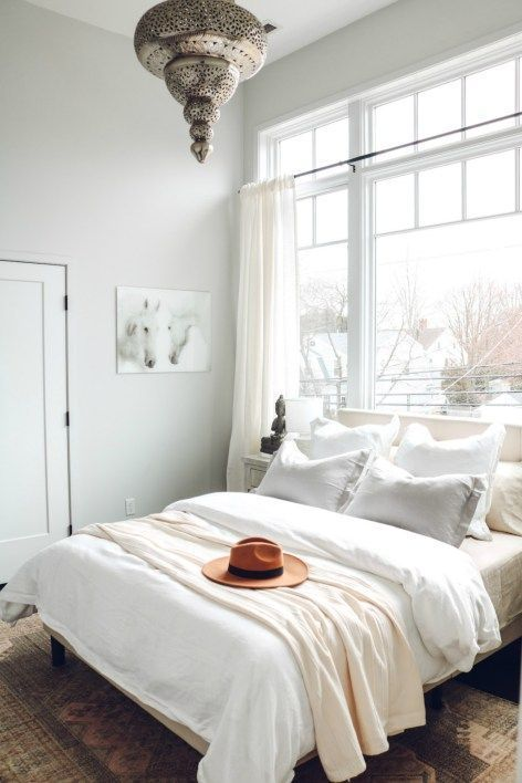 White Boho Bedroom Refresh | Nesting with Grace | Complete with soft layered bedding and neutral colors, this master bedroom makeover has soft linen bedding, a natural vintage rug, and a boho chic lighting for the perfect bedroom retreat.