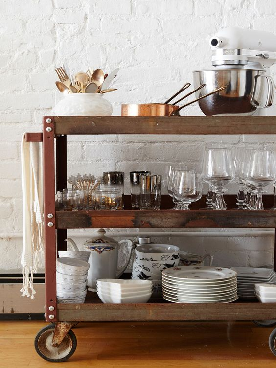 A bar cart from Brooklyn Flea stacked with a variety of dishes and kitchen tools. | Lonny.com