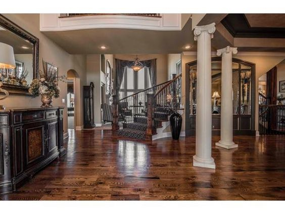 Iron spindles, rich hardwoods, white pillars. Perfection! #entryway #foyer #luxuryhomes