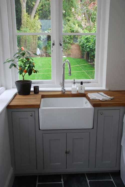 Butler sink, wooden worktop, grey painted units over looking a lovely little garden..