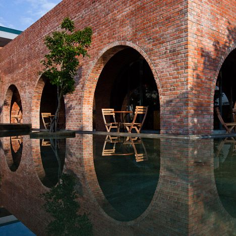 A grid of 24 red brick arches frames the interior of this Vietnam coffee shop by Wangstudio, which sits between a garden and a reflective pool of water / TechNews24h.com