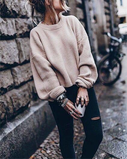 Outfit de jersey holgado en color beige y jeans negros.