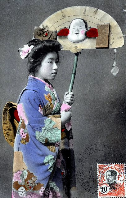 """A Hangyoku (Young Geisha) holding a Kumade or """"Lucky Charm Rake"""", which are sometimes styled to resemble cypress-slat fans, as here. The Otafuku mask or """"Goddess of Mirth"""" is generally attached to help rake in happiness and prosperity. Kumade are sold at Tori-no-Ichi Festivals that are held in November, throughout Japan. The largest of the Tori-no-Ichi Festivals are in Tokyo."""