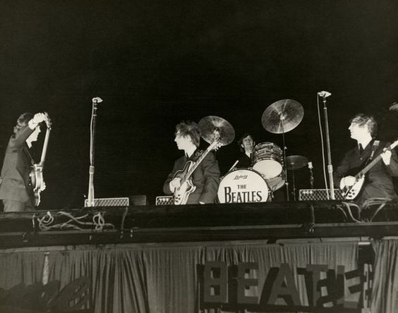 The Beatles prepare to play at the Gator Bowl in Jacksonville, Florida on Sept. 11, 1964. High winds eventually ripped the cardboard letters spelling out Beatles away from the stage, recalled a concertgoer. (Vern Barchard/State Archives of Florida)