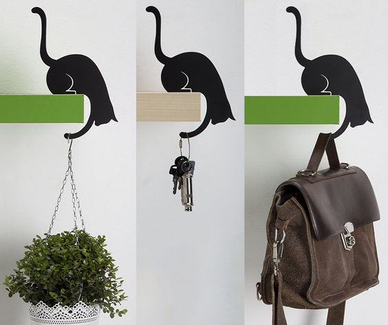 A metal hanger is shaped like the silhouette of black cat and balances upright when an object is placed on its paw.