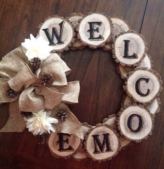 We love this rustic wreath with wood burned welcome letters! You'll need about 20 slices of wood, a wood burning tool, letter stencils, wood tacks or strong glue, and a burlap bow. First trace your...