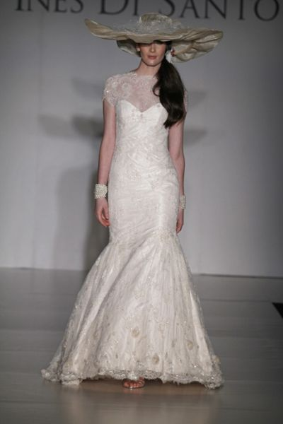 Off white beaded Chantilly Lace gown with high neck and short sleeves. Skirt features three-dimensional  florettes at the hem.