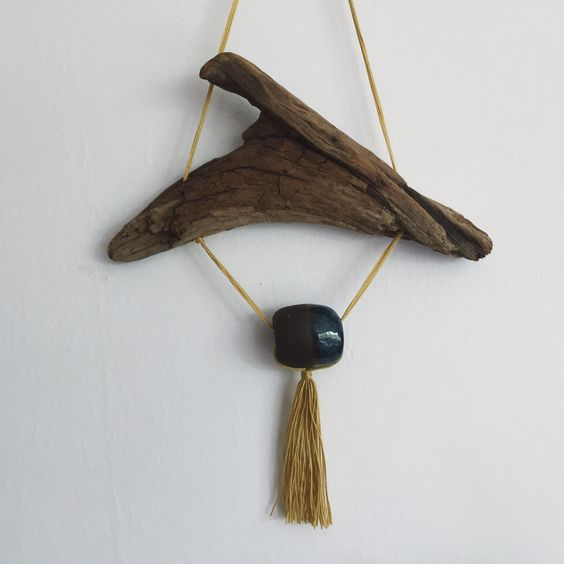 One-of-kind wall hanging made of driftwood with a ceramic bead, partly glazed in dark blue an mustard colored cotton ornament. Hangs in thin, mustard colored cotton string. Note: Unique items including wall hangins like this are currently displayed at Craft