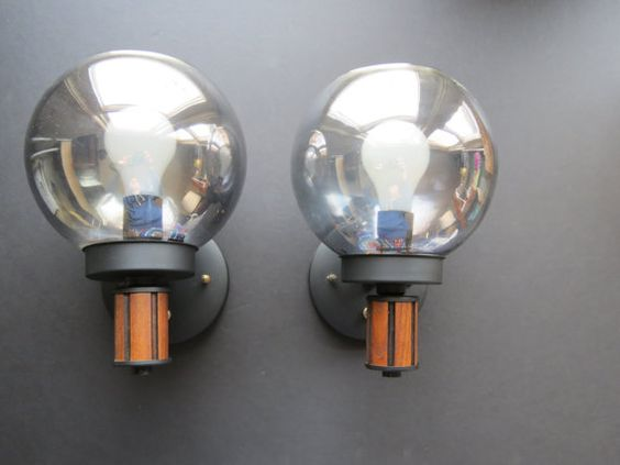 Made in the mid-century era, this is a pair of modern style wall sconces. These lights are composed of black metal bases with wood accents and smoke