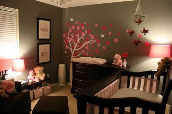 dark wood furniture in the nursery with pink accents and wall decal