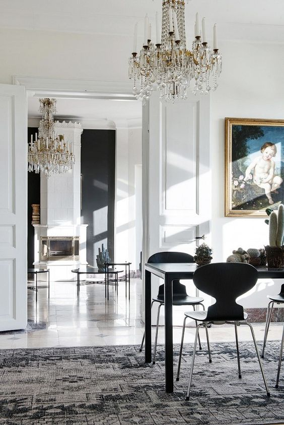 The quirky silhouette of these modern chairs are a great foil to the opulent chandelier and framed art: