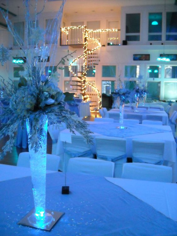 """The bride & groom wanted an """"icy"""" feel, so they used cool white and blue linens, with dramatically lighted centerpieces.  The spiral staircase was the only """"warm"""" lighting in the room, making quite an impact!"""
