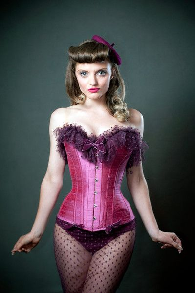 This is our Annie style corset made in a pink silk and trimmed with purple soft polka dot net and finished with velvet bows.