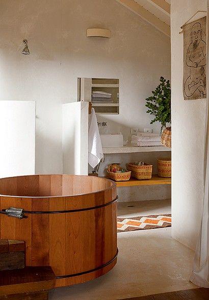 O tecnocimento faz o acabamento do piso, bancada e paredes do boxe deste banheiro assinado pela arquiteta Kita Flórido. O ofurô fica em destaque junto à janela e à porta do terraço