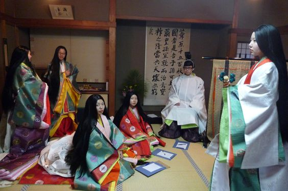 A man and a group of women dressed in heian robes at a junihitoe photography experience.