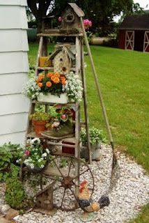 an old ladder decorated with plants and birdhouses