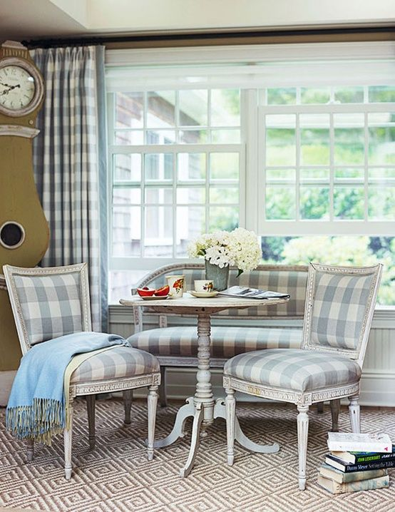 Blue kitchen decor ideas in this charming Swedish style breakfast room with Mora clock, soft blue and white check upholstery, and elegant decor. #bluekitchen #swedish #kitchendecor #breakfastnook #check #moraclock #countrykitchen