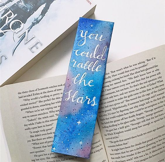 Throne of Glass inspired handmade bookmark with the quote You could rattle the stars  Every bookmark is hand painted with high quality watercolours and this bookmark is lettered with a white gel pen which has a shine on 300 gsm acid free watercolour paper. The bookmark is double sided, with the galaxy style background and quote on the textured side, and a watercolour wash on the back. The dimensions are about 2 x 7.5  Each bookmark will have a slightly different look because they are all uniq...: