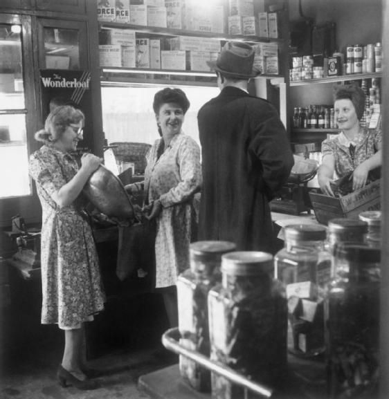 Reverend Joseph Stephens (back to camera) stops in a grocer's shop in Silvertown to buy some cherries. The shop assistant behind the counter on the right of the photograph is preparing to scoop some of the fruit from a box into the scales. To the left of the photograph, two women are weighing vegetables into a sack. The shelves are lined with food, such as 'Force Wheat Flakes', 'Welgar Shredded Wheat' and 'Peter's Cocoa'.