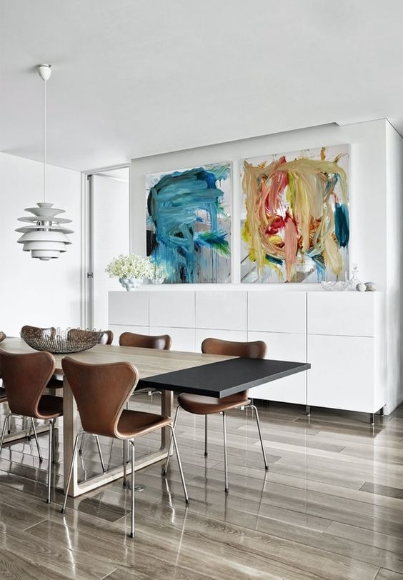Modern and elegant dining room with colorful paintings by the artist Peter Bonde.