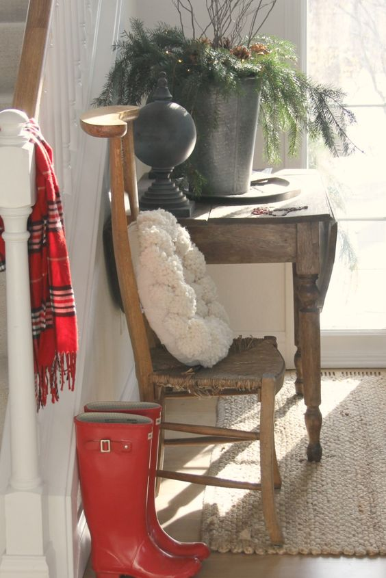 Bright red weliles and a plaid scarf in a country entry with antiques and simple Christmas decor. #hellolovelystudio #christmasdecor #countrychristmas #redboots