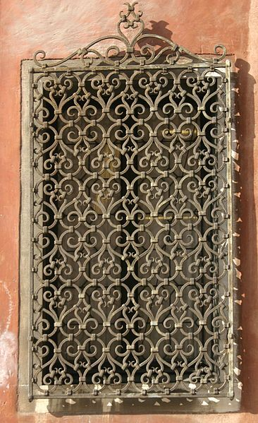 Wrought iron window grille with heart scroll pattern