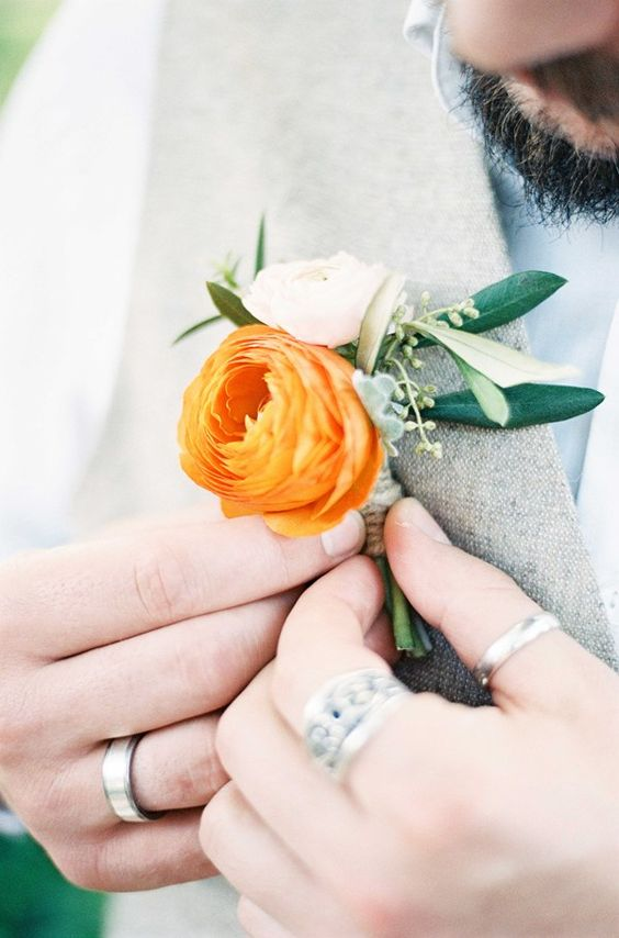 We love the vibrant orange used on this buttonhole.