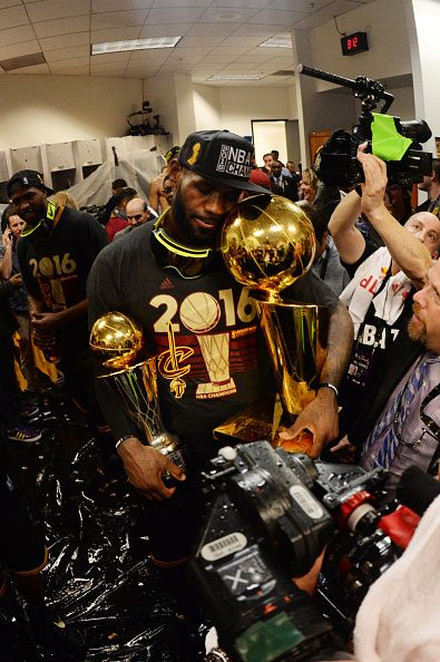 LeBron James of the Cleveland Cavaliers celebrates with the Larry O'Brien NBA Championship Trophy and the Bill Russell NBA Finals Most Valuable...