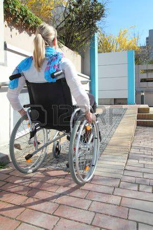 handicaps: Mujer en una silla de ruedas en una rampa para sillas de ruedas