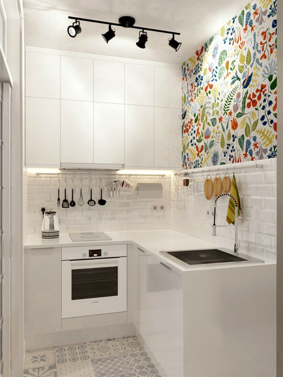 The reflective white flat-panel cabinets make this space feel airier, the backsplash resembling a brick wall is painted in pure white, but in order to enliven this area, a splash of color was added through a multi-color wall floral pattern placed just above the backsplash. The stainless-steel appliances as well as the shiny hardware and fixtures reflect more light, making the small kitchen area feel more expansive.: