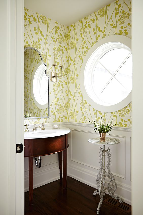 Bold chartreuse wallpaper and round window in classic powder room by #SarahRichardson #traditionaldecor