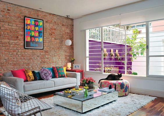A designer espantou a impessoalidade que tanto a incomodava na casa. Na área social, tacões de ipê substituíram o piso frio de porcelanato. Descascada, a parede da sala expõe os tijolos originais dos anos 60.: