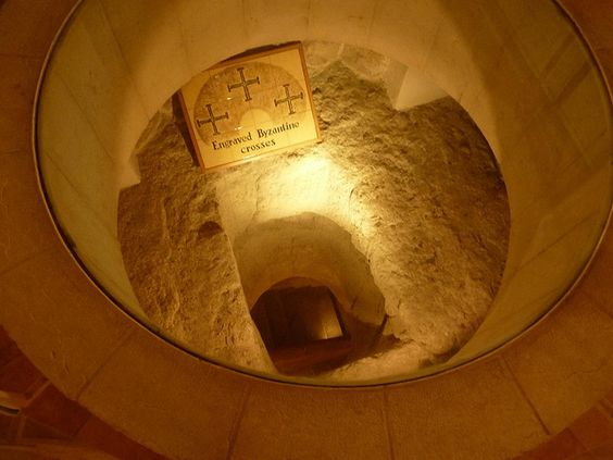 """Alternate view of the hole of Sacred Dungeon at St. Peter in Gallicantu, named after Peter's denial of Jesus before the cock crowed (""""galli cantu""""), is the House of Caiaphas where Jesus was kept in an underground prison like the other criminals of the time period. It's believed he was kept in this old cistern, lowered from the upper level by a rope tied around his waist."""