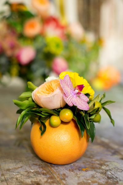 Citrus centerpiece: How beautifully is this orange has been used a cute vase for a tiny floral bouquet! | These 20 Unique Floral Centrepiece Ideas Are Irresistibly Screenshot-Worthy! | Function Mania