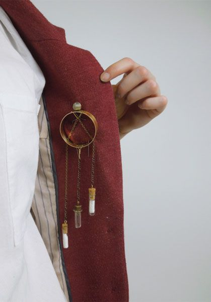 Francesca Lobb, Manchester School of Art - 'Watchmaker's Brooch' – from 'Explore' Collection.  Worn on the inside of the jacket to reflect the significance of the user's personal choice. Brass, chain, stainless steel and corked glass vials -
