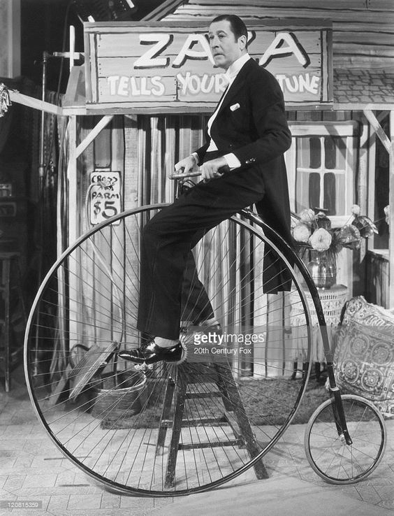 English actor Arthur Treacher (1894 - 1975) on a penny farthing bicycle during filming of 'Step Lively, Jeeves!' directed by Eugene Forde, 1937. Treacher plays the title role in the film adaptation of the P.G. Wodehouse novel.