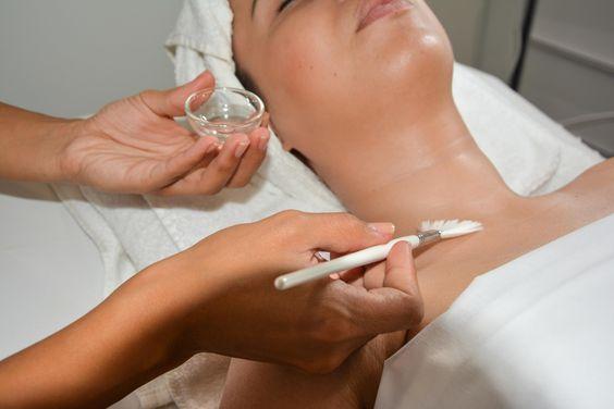 unas manos aplicando un tratamiento facial con pincel sobre el cuello de una paciente